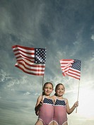 Two young sisters holding American flags
