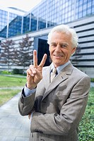 Germany, Baden Württemberg, Stuttgart, Senior businessman making peace sign, smiling, portrait