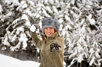 Austria, Salzburger Land, Altenmarkt, Young woman throwinh snowball