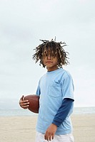 Mixed Race boy holding football