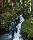 Multi_ethnic businessmen climbing up waterfall