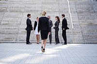 Germany, Baden_Württemberg, Stuttgart, Businessswoman walking, businesspeople waiting in background