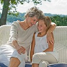 Grandmother and granddaughter sitting on porch