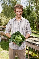 Man holding savoy cabbage, portrait