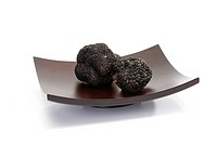 Black truffles on wooden bowl, close_up
