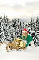 Austria, Salzburger Land, Altenmarkt, Young woman pushing sledge with Christmas presents