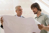Two men looking at construction plan, portrait