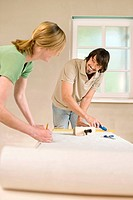 Young couple renovating, measuring wallpaper