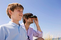 Germany, Baltic sea, Father and son 8_9, father looking through binoculars, portrait