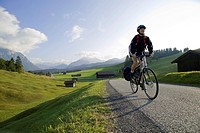 Germany, Bavaria, Mittenwald, Woman mountain biking across highway