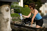 Germany, Bavaria, Seeshaupt, Woman filling water bottle