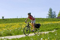 Germany, Bavaria, Oberland, Woman mountain biking across farm track