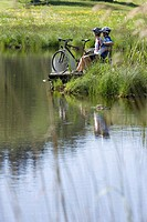 Germany, Bavaria, Couple with mountain bikes relaxing on lakeshore