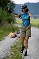 Germany, Bavaria, Oberland, Woman gesturing, fallen biker in background
