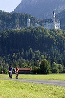 Germany, Bavaria, Neuschwanstein Castle, Couple mountain biking