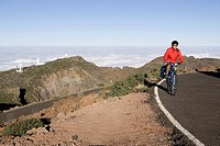 Spain, The Canary Islands, La Palma, Woman mountain biking on highway