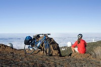 Spain, The Canary Islands, La Palma, Woman with mountain bike taking a break, looking over clouds