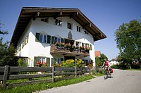 Germany, Bavaria, Lenggries, Woman mountain biking next to residential house