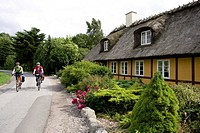 Denmark, Fuenen, Couple mountain biking alongside thatched house