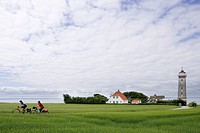 Denmark, Fuenen, Couple mountain biking across farm track, lighthouse in background