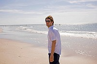 Germany, Baltic sea, Young man standing on beach