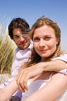 Germany, Baltic sea, Young couple sitting in dunes, portrait