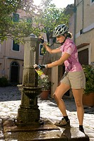 Italy, Tuscany, Elba, Poggio, Female mountainbiker filling water bottle