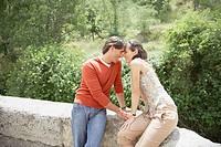 Romantic couple resting on stone bridge