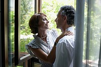 Romantic couple hugging near window