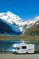 Person standing next to a RV, views Byron Peak & Portage Lake in Portage Valley, Southcentral, Alaska