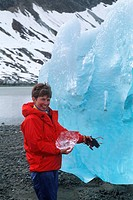 Woman holds a small chunk of ice next to a large grounded iceberg at Reid Inlet in Glacier Bay National Park in Southeast Alaska