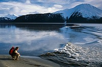 Woman hiking along Turnagain Arm stops to observe an incoming Bore Tide. Summer in Southcental Alaska.