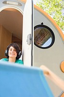 Germany, Leipzig, Ammelshainer See, Young woman in camping trailer listening to headphones