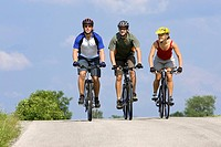 Germany, Bavaria, Oberland, Three mountain bikers riding across highway