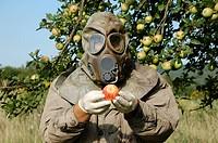 Mann mit Gasmaske hält einen Apfel