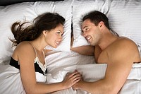 A couple lying in bed face to face