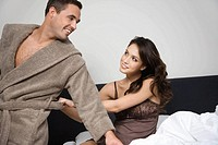 A woman pulling at a mans bathrobe