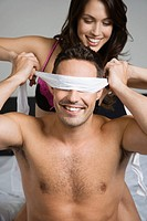 A woman blindfolding a man