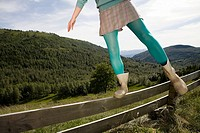 Woman balancing on a wooden fence