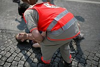 EMERGENCY AID WORKER Photo essay. Paris Marathon, April 2007. First aid attendant from the French Red Cross with an injured person.