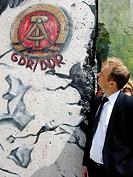 Geschäftsmann vor Berliner Mauer