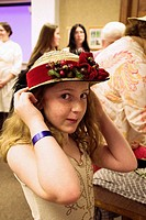 11-year-old girl trying on 19th century hat at Monroe County historical museum, Indiana, USA