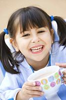 Close_up of a happy young girl holding a chocolate cup
