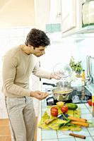 Young man preparing food in kitchen