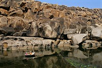 Foreigners enjoying coracle ride in Tungabhadra river , Hampi , Hospet , Karnataka , India