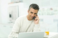 Man talking on cell phone, sitting by laptop and orange juice