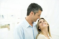 Couple smiling at each other, woman leaning against man