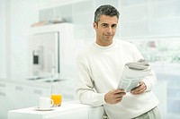 Man leaning against kitchen counter, holding newspaper, smiling at camera