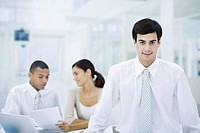 Businessman in office, smiling at camera, employees working in background