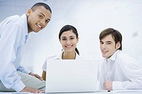 Young professionals gathered around laptop computer, smiling at camera